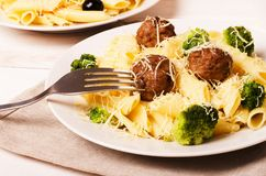 Pasta penne with meatballs and broccoli. With fork on a plate Stock Photo