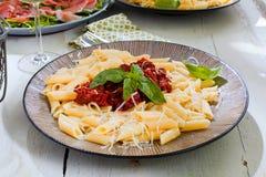 Pasta Penne med Bolognese sås för tomat, parmesanost och basilika arkivbilder