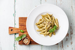 Pasta Penne with pesto. Sauce and pine nuts on wooden background Royalty Free Stock Photography