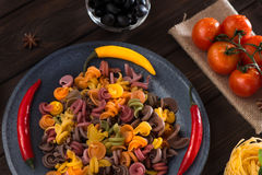 Pasta and pepper on a gray plate with tomatoes, sweet pepper, lemon, olives on a wooden dark background. Ingredients for Royalty Free Stock Images