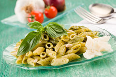 Pasta with pesto on green glass table Stock Image