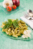 Pasta with pesto on green glass table Royalty Free Stock Photography