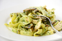 Pasta with pesto, mushrooms and chicken on white plate Royalty Free Stock Photo