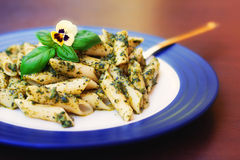 Pasta with pesto sauce decorated with an edible flower Royalty Free Stock Photo