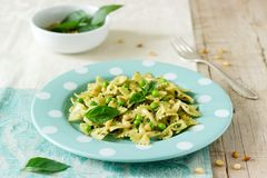 Pasta with pesto sauce, green peas and basil on a wooden table. Rustic style. royalty free stock image