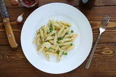 Pasta with pesto sauce, green peas, garlic and dill on a white plate on a wooden table. Lie next to a fork and knife, sun dried royalty free stock photo