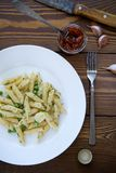 Pasta with pesto sauce, green peas, garlic and dill on a white plate on a wooden table. Near are a fork,a knife and sun-dried stock photography