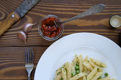 Pasta with pesto sauce green peas garlic and dill on a white plate wooden table. The view from the top. Italian cuisine. stock photos