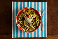 Pasta with pesto sauce, parmesan on gingham plate, turquoise nap Royalty Free Stock Photography