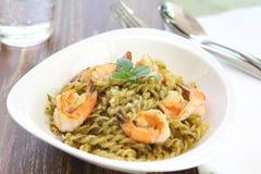 Pasta with pesto sauce and prawn. On a dish Stock Image