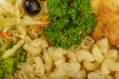 Pasta with a piece of grilled meat and salad. stock image