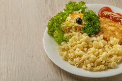 Pasta with a piece of grilled meat and salad. stock images