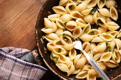 Pasta with pieces of fried onions. And spinach Royalty Free Stock Photos