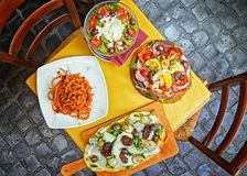 Pasta , pizza , salad and homemade food arrangement in a restaurant Rome stock images