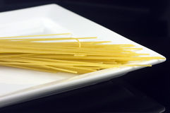 Pasta and plate. Uncooked pasta on a dinner plate Royalty Free Stock Image