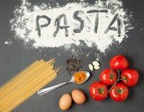 Pasta, pomodori, aglio, farina ed uova crudi sul fondo di legno nero della tavola, vista superiore Immagini Stock