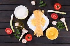 Pasta, pomodori, funghi, farina ed uovo crudi sul fondo di legno nero della tavola Fotografia Stock