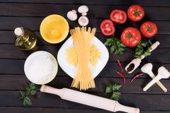 Pasta, pomodori, funghi, farina ed uovo crudi sul fondo di legno nero della tavola Immagini Stock