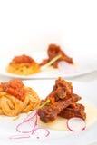 Pasta with pork ribbs sauce on polenta bed Stock Photo