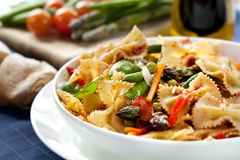 Pasta Primavera. Fresh bow-tie pasta with asparagus, beans, peas, snow-peas, tomatoes, carrots and peppers Stock Images