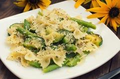 Pasta Primavera - ` piatti deliziosi, calorosi e sani di s dall'Italia del sud Fondo rustico di legno con i fiori top Fotografia Stock
