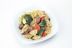Pasta Primavera with Sausage. White Bowl of Bowtie Pasta Primavera with Sausage isolated on a white background royalty free stock image