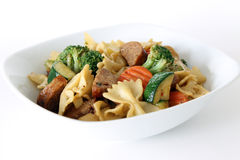 Pasta Primavera with Sausage. Bowtie pasta primavera with sausage in a white bowl on an isolated background, made with zucchini, broccoli, carrot, sausage royalty free stock photography