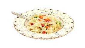 Pasta Primavera in southwestern bowl with fork. A single serving of pasta Primavera in a southwestern style bowl with fork on a white background Stock Photo