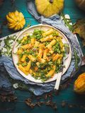 Pasta with pumpkin and arugula. Pasta with baked pumpkin, arugula and onion. Rustic green autumn background with pumpkins and dry leaves. Fall food still life royalty free stock photo