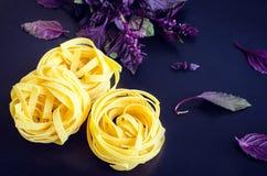 Pasta with purple basil on dark background. Tagliatelle with fresh purple basil on dark background. Traditional Italian pasta. Selective focus Stock Image