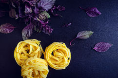 Pasta with purple basil on dark background. Tagliatelle with fresh purple basil on dark background. Traditional Italian pasta. Top view Stock Image