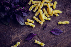 Pasta with purple basil on wooden background. Fusilli with fresh purple basil on wooden background. Traditional Italian pasta.Top view Royalty Free Stock Photos