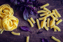 Pasta with purple basil on wooden background. Fusilli and tagliatelle with fresh purple basil on old rustic wooden background. Traditional Italian pasta. Top Royalty Free Stock Photo