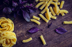 Pasta with purple basil on wooden background. Fusilli and tagliatelle with fresh purple basil on old rustic wooden background. Traditional Italian pasta. Top Stock Photos