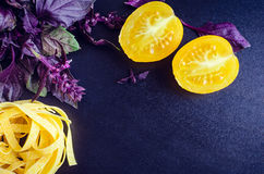 Pasta with purple basil and yellow tomatoes on dark background. Tagliatelle with fresh purple basil and yellow tomatoes on dark background with place for text Royalty Free Stock Photo