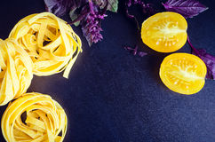 Pasta with purple basil and yellow tomatoes on dark background. Tagliatelle with fresh purple basil and yellow tomatoes on dark background with place for text Stock Photography