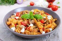 Pasta Radiatori with chicken, mushrooms, cherry tomatoes, feta cheese and tomato sauce Stock Photo