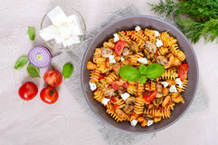 Pasta Radiatori with chicken, mushrooms, cherry tomatoes, feta cheese and tomato sauce on a light background. Stock Photo
