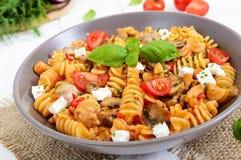 Pasta Radiatori with chicken, mushrooms, cherry tomatoes, feta cheese and tomato sauce Stock Images
