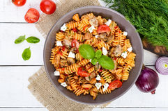 Pasta Radiatori with chicken, mushrooms, cherry tomatoes, feta cheese and tomato sauce on a white wooden background. Royalty Free Stock Images