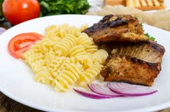 Pasta Radiatori and fried rabbit ribs. Stock Images