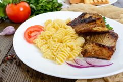 Pasta Radiatori and fried rabbit ribs. Stock Image