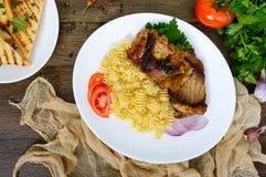 Pasta Radiatori and fried rabbit ribs. Stock Photos