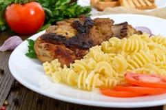 Pasta Radiatori and fried rabbit ribs. Royalty Free Stock Image