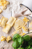 Pasta ravioli on flour with basil Stock Photos