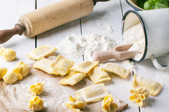 Pasta ravioli on flour. Close up of homemade pasta ravioli and perle on wooden table with metal mug of flour. See series Royalty Free Stock Images
