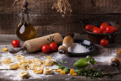 Pasta ravioli on flour. Homemade pasta ravioli on old wooden table with flour, basil, tomatoes, olive oil and vintage kitchen accessories Stock Images