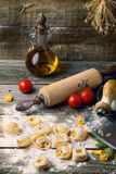 Pasta ravioli on flour. Homemade pasta ravioli on old wooden table with flour, basil, tomatoes, olive oil and vintage kitchen accessories. See series Royalty Free Stock Images
