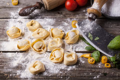 Pasta ravioli on flour. Homemade pasta ravioli on old wooden table with flour, basil, tomatoes and vintage kitchen accessories Stock Image