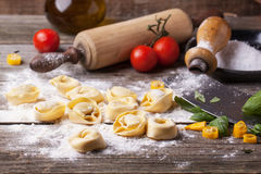 Pasta ravioli on flour. Homemade pasta ravioli on old wooden table with flour, basil, tomatoes and vintage kitchen accessories. See series Stock Image